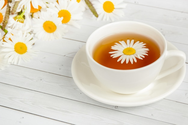Taza de té de manzanilla en una mesa de madera blanca. copia espacio