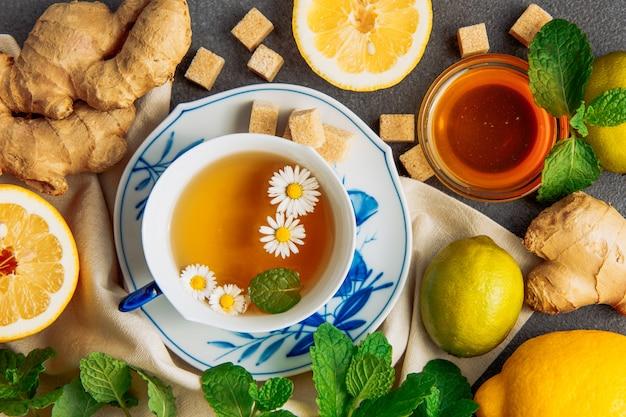 Taza de té de manzanilla con rodajas de limón, jengibre, terrones de azúcar morena, miel en un tazón de vidrio y hojas verdes en un plato sobre fondo gris y un trozo de tela, plana.
