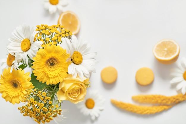 Taza de té de margaritas con rodaja de limón y flores de manzanilla fresca en un jarrón