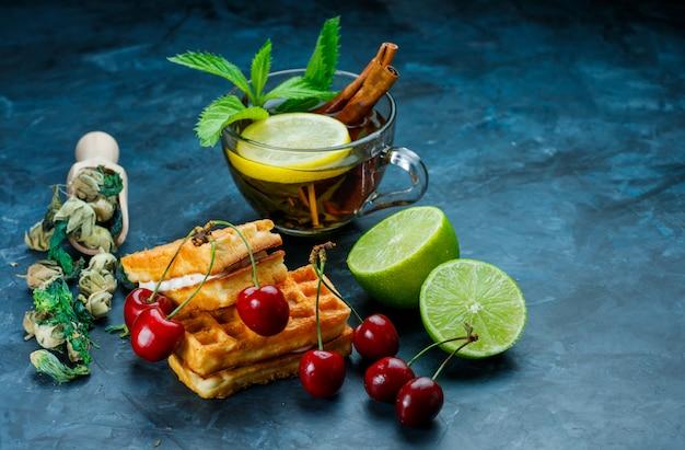 Taza de té con menta, canela, hierbas secas, cereza, lima sobre superficie azul sucio, vista de ángulo alto.
