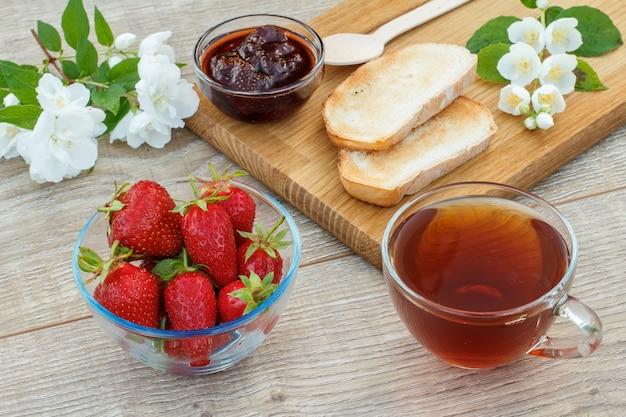 Taza de té, mermelada de fresa casera, pan sobre tabla de cortar de madera y fresas frescas