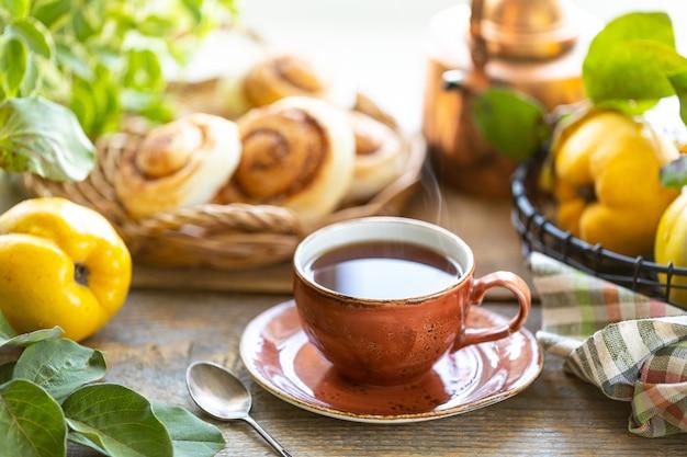 Taza de té con mermelada de membrillo casera sobre un fondo de madera vieja. frutas frescas y hojas de membrillo en el fondo. foto horizontal. rústico