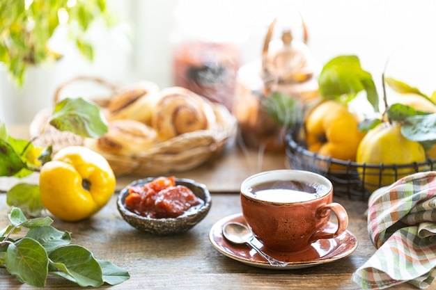Taza de té con mermelada de membrillo casera en una vieja mesa de madera. frutas frescas y hojas de membrillo
