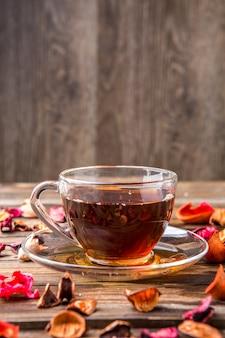 Taza de té en mesa con pétalos