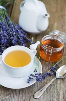 Taza de té y miel con flores de lavanda.
