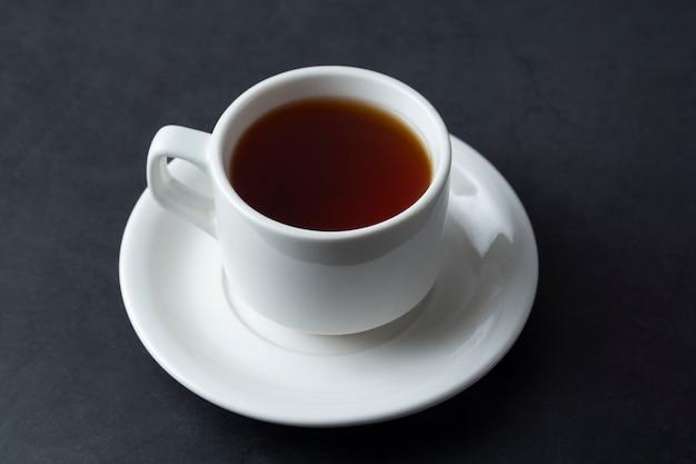 Una taza de té negro aislada sobre oscuridad con copyspace.