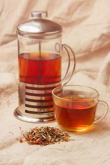 Taza de té negro caliente, hojas de té secas sobre una tela ligera