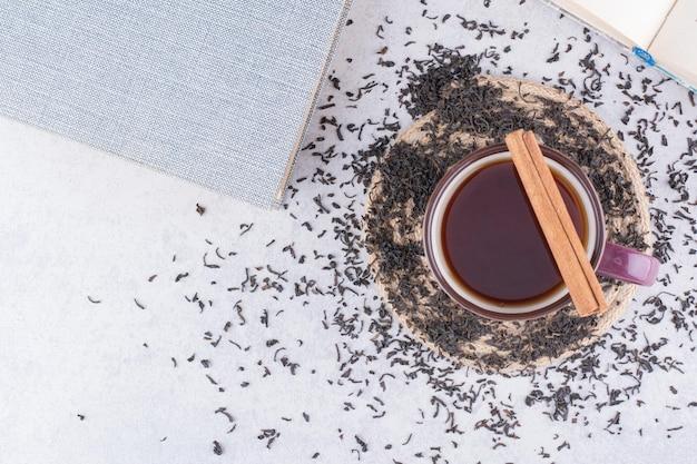Taza de té negro con canela en rama y té seco
