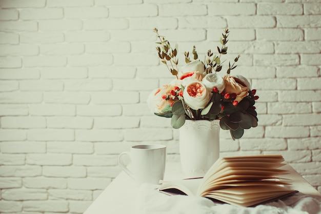 Una taza de té negro, cuaderno y hermosas flores sobre la mesa. inspiración matutina para la planificación del día.