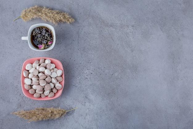 Taza de té negro con cuenco de caramelos marrones sobre fondo de piedra.