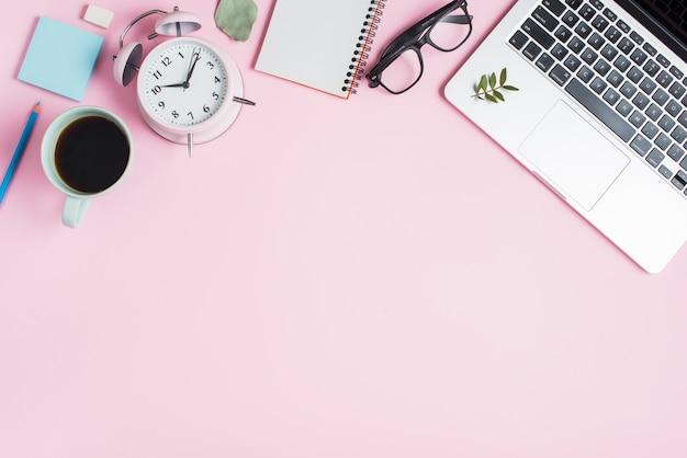 Taza de té negro; despertador; bloc de notas espiral anteojos y laptop sobre fondo rosa