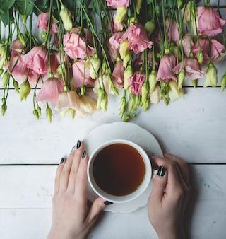 Una taza de té negro y flores amarillas y rosadas