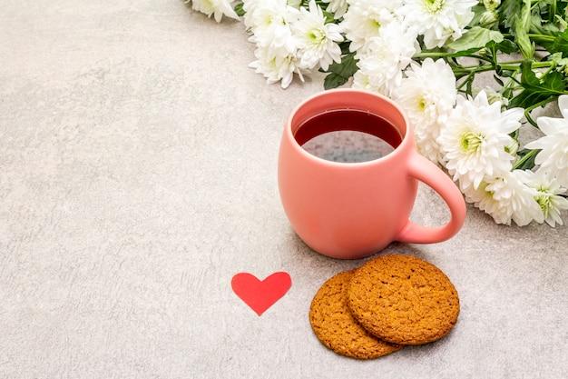 Taza de té negro, galletas de avena y ramo de crisantemos