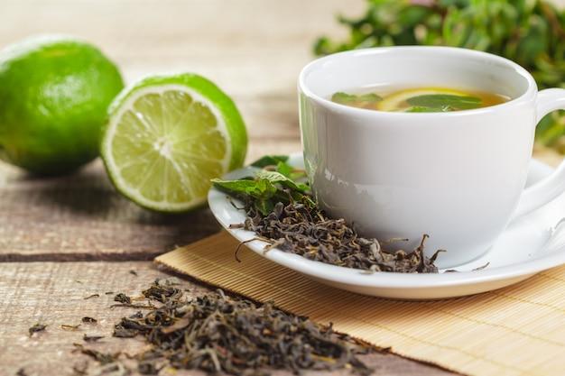 Taza de té negro con hojas de menta en una mesa de madera