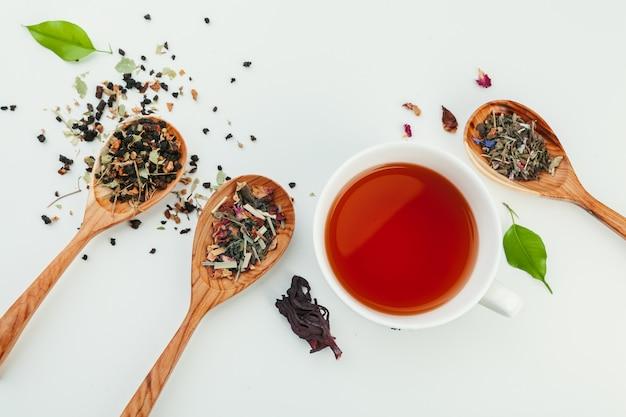 Taza de té negro y hojas sobre un fondo blanco.