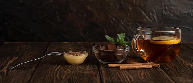 Una taza de té negro con limón cerca de chocolate y miel.