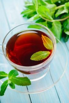 Taza de té negro con menta fresca