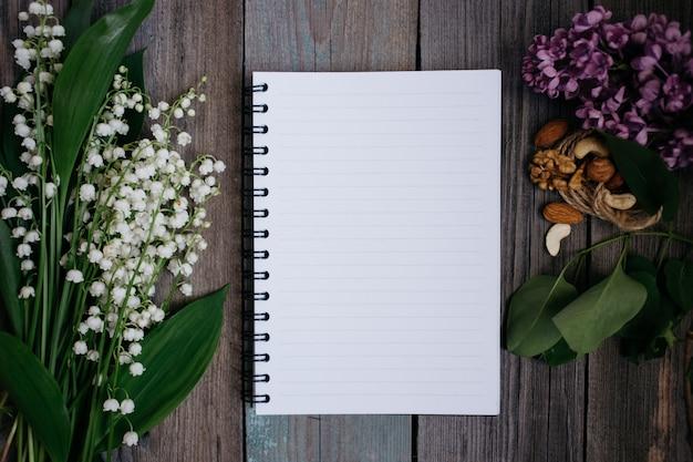 Una taza de té, nueces, lilas y un cuaderno sobre un fondo de madera