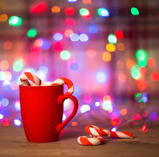 Taza de té o café. dulces. decoraciones de navidad. bolas rojas y campanas. fondo de madera.