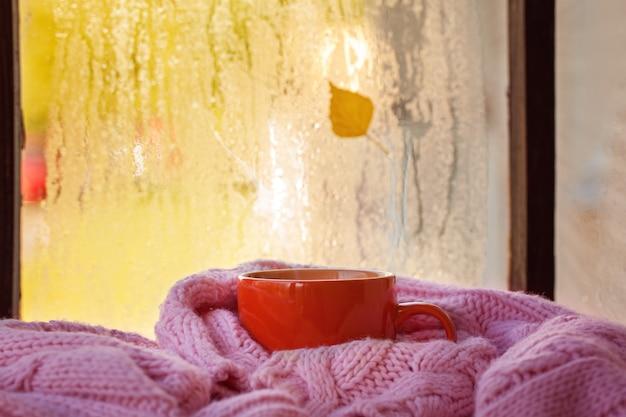 Taza de té o café de otoño y hojas amarillas en una ventana lluviosa