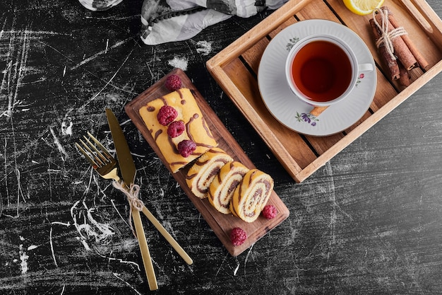 Una taza de té con pastel de rollo, vista superior.