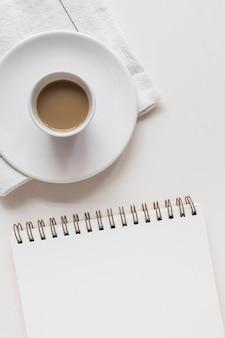 Taza de té y platillo sobre la servilleta con bloc de notas espiral sobre fondo blanco