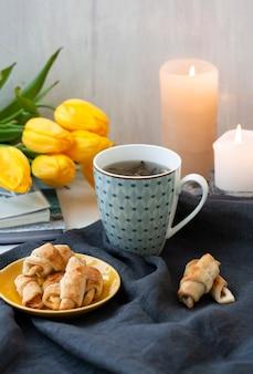 Taza de té, un plato de galletas, flores de tulipán amarillo y velas.