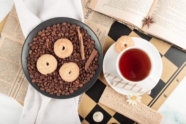Taza de té y plato de galletas en un tablero de ajedrez