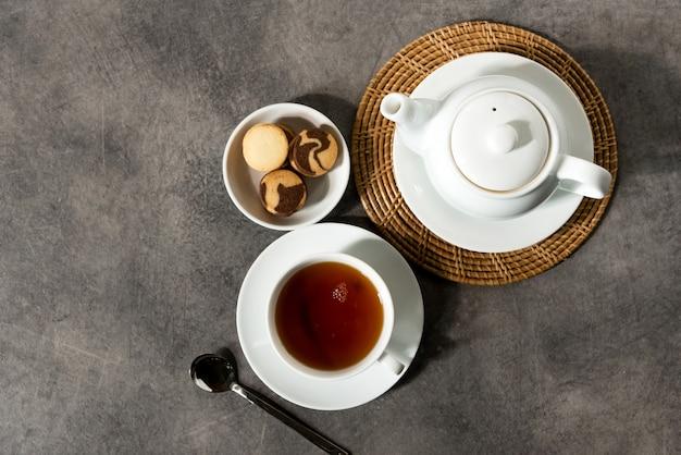 Taza de té de porcelana blanca y tetera, té inglés en la mesa, té de la tarde