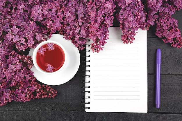 Taza de té y ramas de flores de primavera ramo lila floreciente en mesa negro. cuaderno diario de mujer.