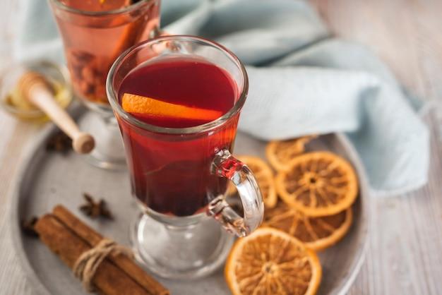Taza de té con rodajas de naranja y canela.