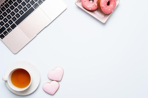 Taza de té y rosquillas rosas con laptop sobre una mesa