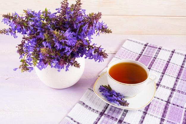 Taza de té en servilleta a cuadros y flores de color púrpura