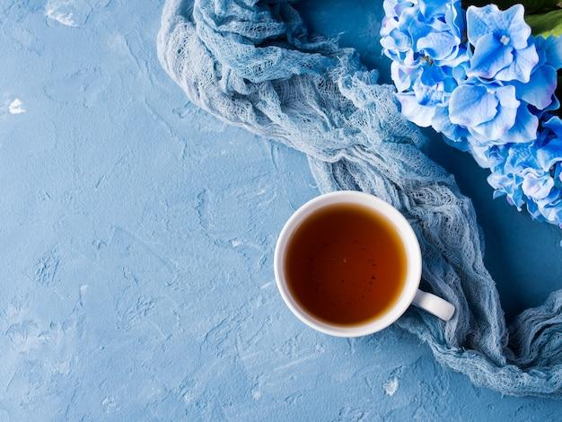 Taza de té sobre fondo azul con flores y textiles