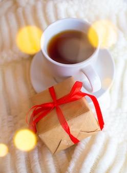 Taza con té sobre un fondo claro y un regalo para el día de san valentín. romántico desayuno del día de la madre.