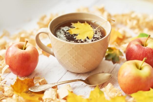 Taza con té sobre un fondo de otoño con manzanas, hojas y flores.