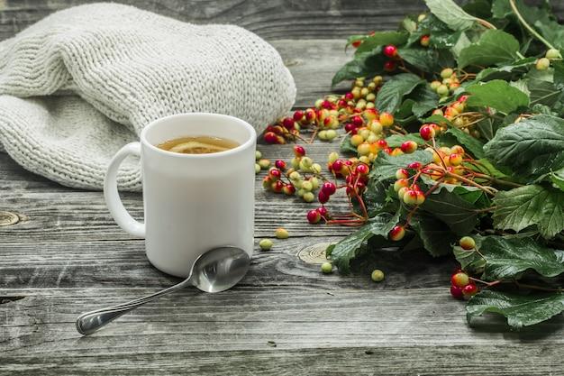 La taza de té sobre un hermoso fondo de madera con suéter de invierno, bayas, otoño