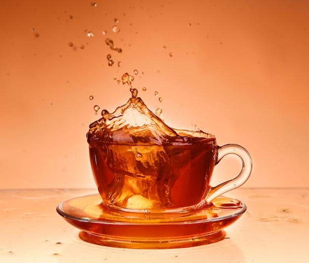 Taza de té sobre vidrio con fondo naranja