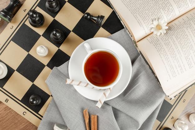 Una taza de té en un tablero de ajedrez y un libro.