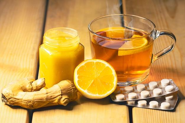 Taza de té y un tarro de miel sobre una mesa de madera