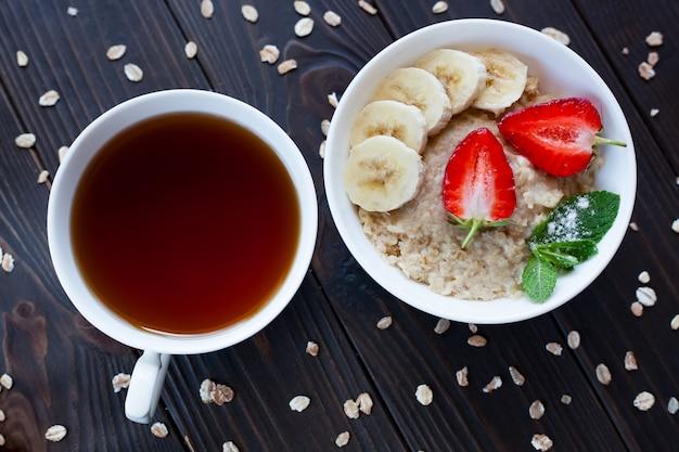 Taza de té y un tazón de avena casera con fresas y plátano sobre una mesa marrón