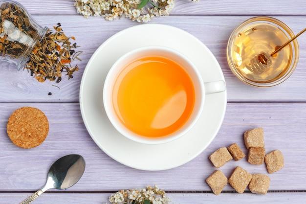 Taza de té con terrones de azúcar y ramas de flores en la mesa de madera de cerca