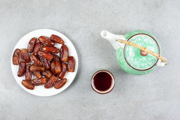 Una taza de té y una tetera adornada junto a un plato de dátiles frescos sobre fondo de mármol. ilustración de alta calidad