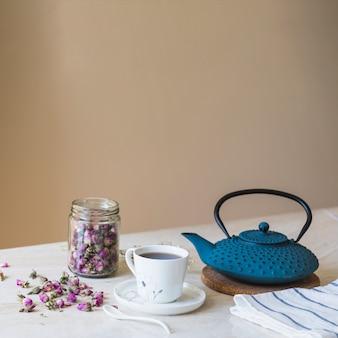Taza de té con tetera y elementos de desayuno