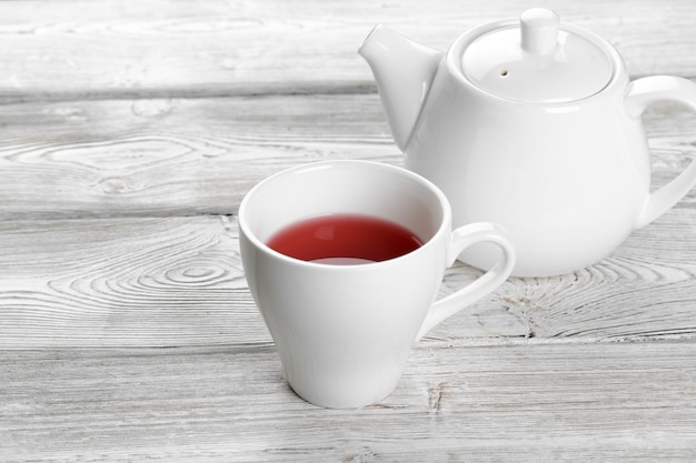 Taza de té y tetera en la mesa