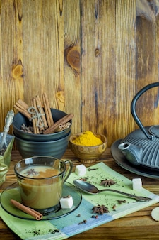 Una taza de té tradicional indio té masala con ingredientes para preparar. canela, anís, azúcar, té negro, pimienta, clavo, cúrcuma en una mesa de madera.