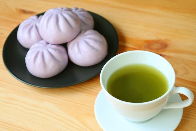 Taza de té verde con borrosa pila de bollos morados de camote al vapor en la mesa de madera