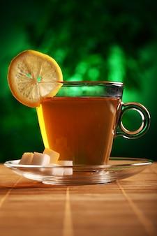 Taza de té verde caliente con azúcar y limón.