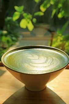 Taza de té verde japonés matcha caliente con latte art en la luz del sol, plantas verdes borrosas en el fondo