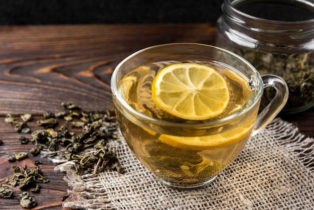Taza de té verde con limón sobre fondo de madera
